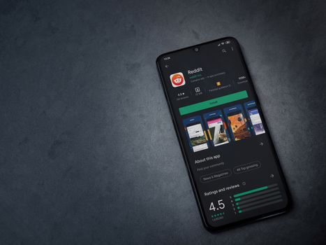 Lod, Israel - July 8, 2020: Reddit app play store page on the display of a black mobile smartphone on dark marble stone background. Top view flat lay with copy space.