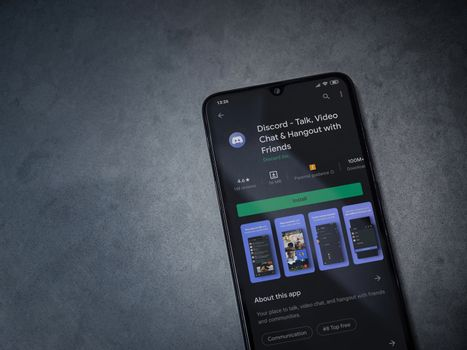 Lod, Israel - July 8, 2020: Discord app play store page on the display of a black mobile smartphone on dark marble stone background. Top view flat lay with copy space.