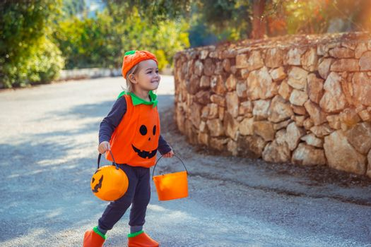 Nice Little Baby Dressed in Pumpkin Character Outfit On The Way to Collect Candies from the Neighbors. Trick or Treat. Kids Enjoying Happy Autumn Holiday.