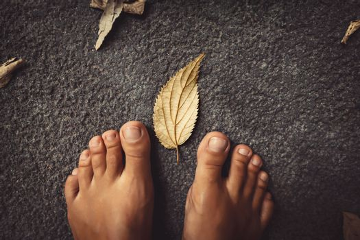 Welcome Fall Background. Closeup Concept Photo of a Barefoot Women Feet and Dry Leaves. Autumn Season Theme.
