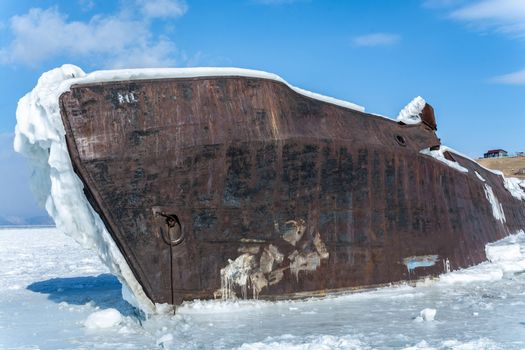 Ship in ice lake against blue sky in winter