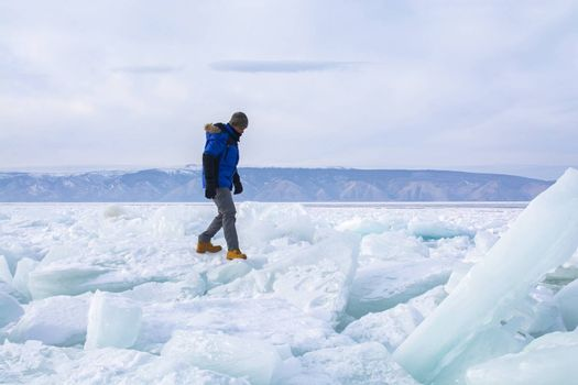 Man walking on broken ice in Lake Baikal, Russia, landscape photography