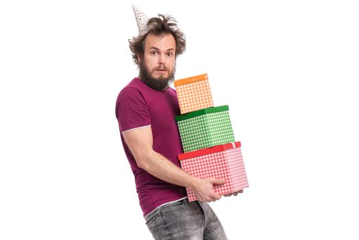 Crazy bearded Man with funny Haircut in birthday cap, isolated on white background. Surprised guy holding many gift boxes. Holidays concept.