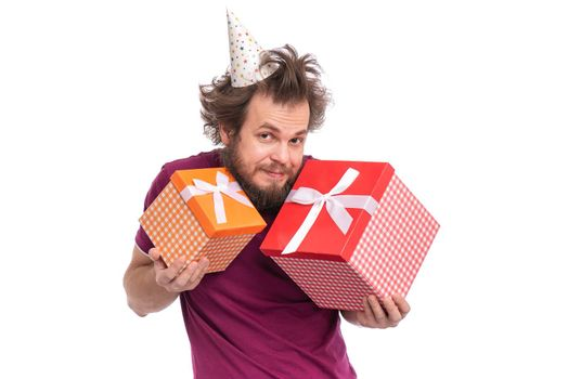 Crazy bearded Man with funny Haircut in birthday cap, isolated on white background. Happy guy holding gift boxes. Holidays concept.