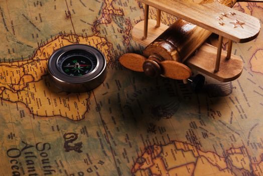 Old compass discovery and wooden plane on vintage paper antique
