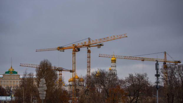 February 5, 2020, Moscow, Russia Construction cranes in front of the cathedrals of the Moscow Kremlin and the bell tower of Ivan the Great