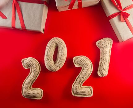 Christmas background with chroched 2021 number and craft paper gift boxes with red ribbons