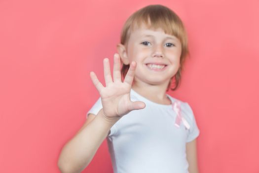 Little girl showing five fingers sign wearing white t-shirt and with pink breast cancer awareness ribbon