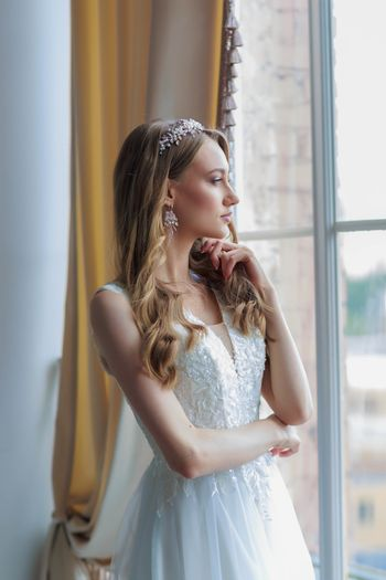 Close-up portrait of the bride in a white wedding dress by the window, looks attentively