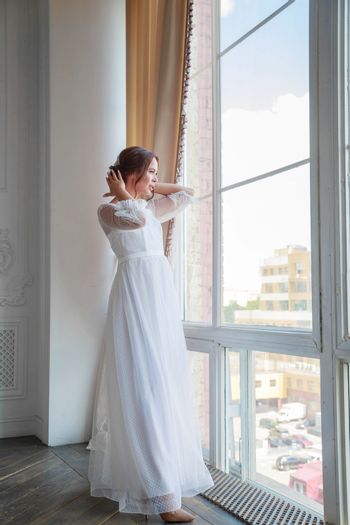 A bride in a white wedding dress straightens her hair while standing by a huge floor-length window.