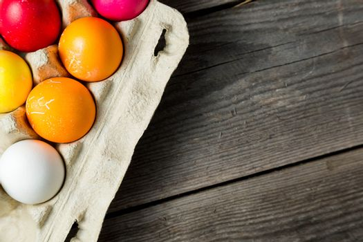 Dyed easter eggs in cardboard box on wooden background. Easter background with space for a text.