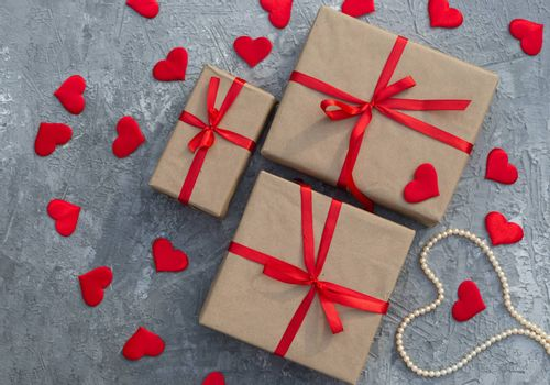 Romantic background with gifts tied with a red ribbon and red hearts on concrete