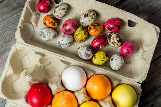 Dyed easter eggs in cardboard box on wooden background. Easter background