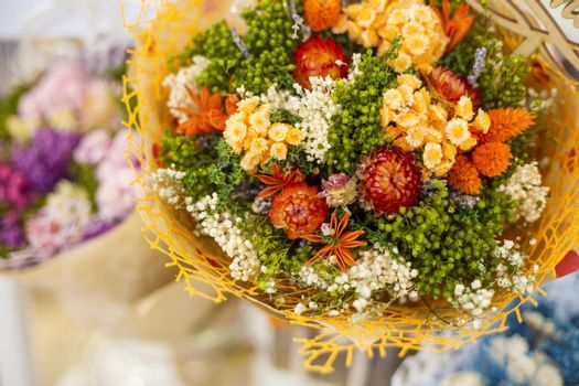 A bouquet of dried meadow plants and flowers for home decoration with a floral multicolored grass in a soft selective focus.
