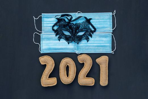 .New year in the context of coronavirus knitted numbers 2021 on medical mask on chalk board