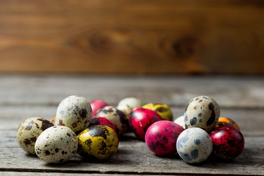 Painted easter eggs in small groups on wooden background. Easter background
