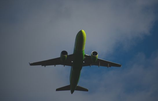 Silhouette of a green plane taking off against a blue sky