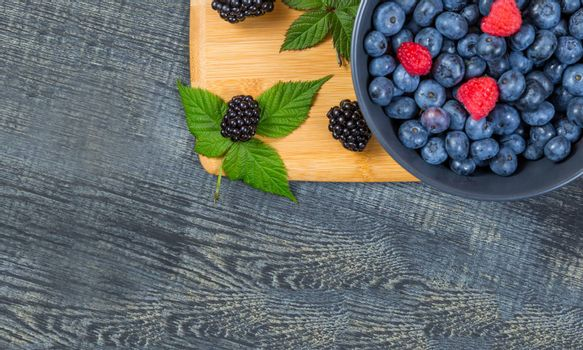 blueberry berry in dark gray ceramic bowl on wooden cutting board on dark blue wooden background. top view soft focus