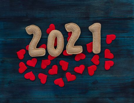 Romantic christmas background with knitted number 21 and red hearts on blue wooden backdrop