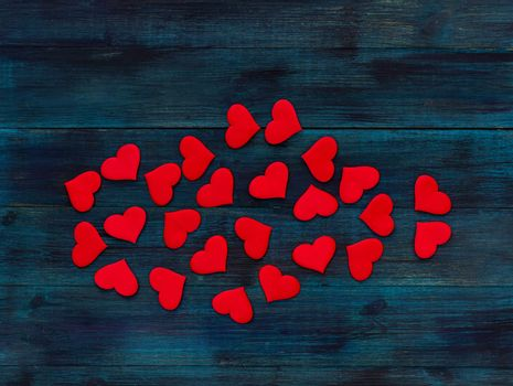 .Romantic valentine's day background red satin hearts on dark blue wooden backdrop