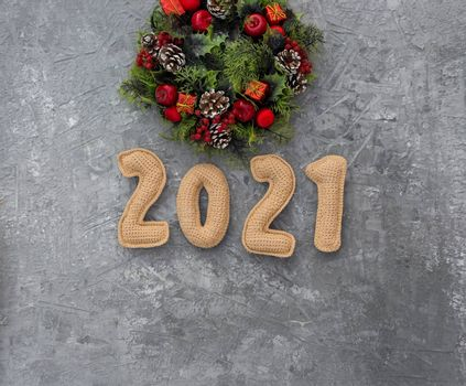 .Christmas background with knitted numbers 2021 and decorative wreath