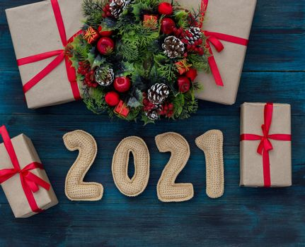 .Christmas background with knitted numbers 2021, gifts tied with a red ribbon and decorative wreath