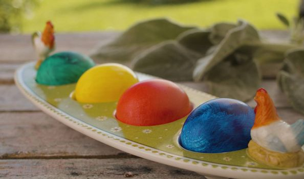 Close up multicolored painted Easter eggs in egg box and rabbits ear plant on wooden table in the garden. Holiday concept