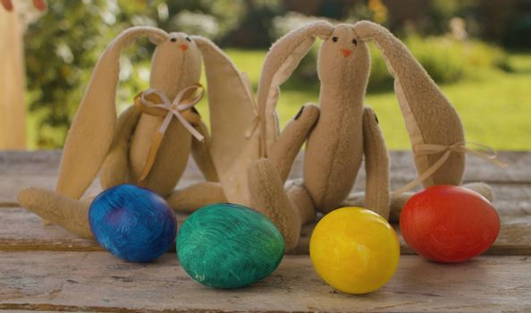Close up multicolored painted Easter eggs and two Easter bunnies on wooden table in the garden. Holiday concept