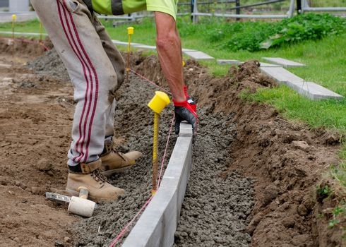 new footpath construction, groundworker/roadworks is placing edg