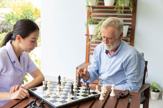 Senior retirement man playing chess with nurse at home