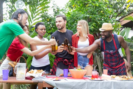 Group of friends having fun and happy in barbecue party at house backyard