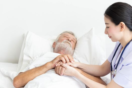 Nurse cares for elderly man sleeping in bed