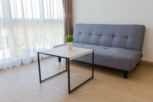Comfortable sofa with table and small plant in living room