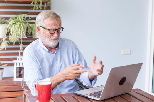 Senior retirement man is working with his laptop at home feeling unhappy