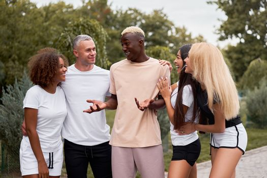 Multi-ethnic group teenage friends. African-american asian caucasian student spending time together Multiracial friendship Happy smiling People dressed black white sportswear meeting outdoor