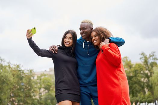 Multi ethnic friends outdoor taking a selfie on smartphone. Diverse group people Afro american asian spending time together Multiracial male female student meeting outdoors
