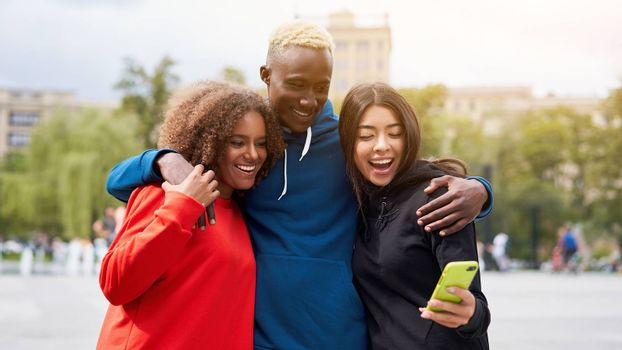Multi ethnic friends outdoor looking smartphone screen. Diverse group people Afro american asian spending time together Multiracial male female student meeting outdoors