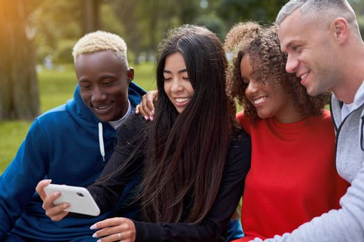 Multi ethnic friends outdoor taking a selfie on smartphone. Diverse group people Afro american asian spending time together Multiracial male female student sitting bench park outdoors