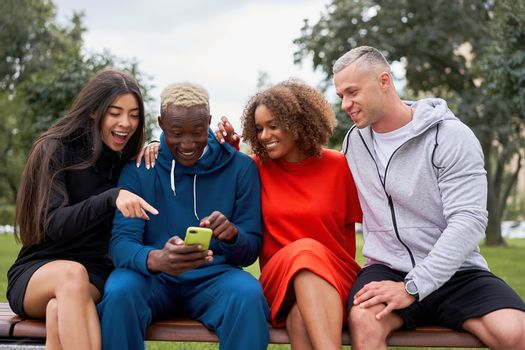Multi ethnic friends outdoor looking smartphone screen. Diverse group people Afro american asian caucasian spending time together Multiracial male female student meeting outdoors