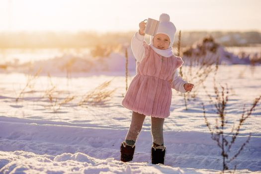 .A little girl stands with a mug of hot chocolate in the middle of a field in winter in the setting sun