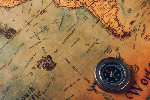 Old compass discovery on vintage paper antique world map