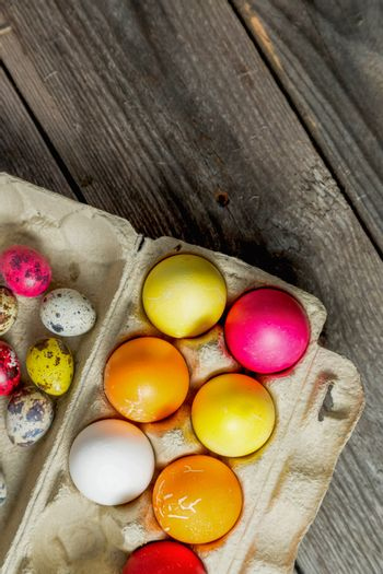 Dyed easter eggs in cardboard box on wooden background. Easter background with space for a text.Vertical high quality photo