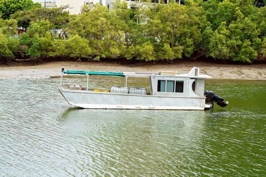 An Old Aluminium Boat Anchored On The River