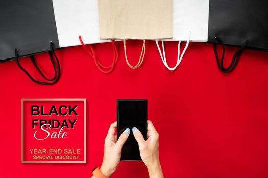black friday sale, woman hand online shopping on smartphone with shopping bag on red background