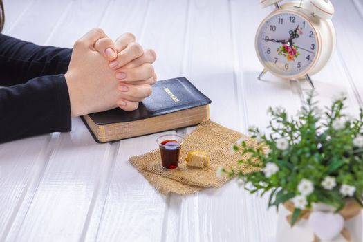 Young woman praying and Taking communion  - the wine and the bread symbols of Jesus Christ blood and body with Holy Bible. Easter Passover and Lord Supper concept Focus on her hands.
