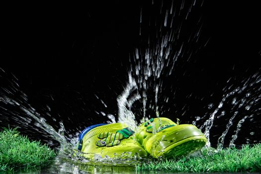 Shoes, water and green grass on a black background
