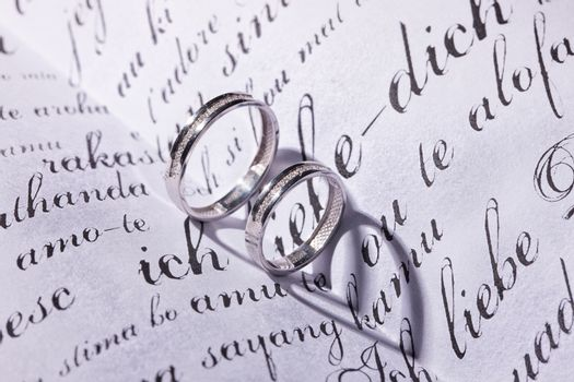 Two wedding rings and shadows on a book