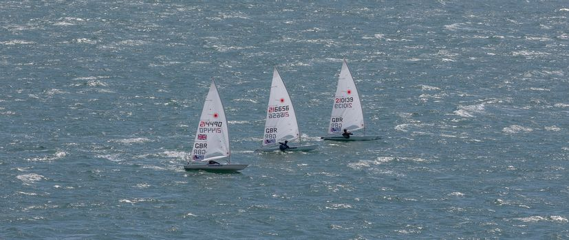 Portland harbour, United Kingdom - July 3, 2020: High Angle aerial panoramic shot of three laser class racing dinghies sailing close to each other in Portland harbour.