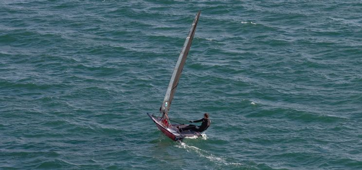 Portland harbour, United Kingdom - July 2, 2020: High Angle aerial panoramic shot of a single racing boat in Portland harbour. Man wearing black swim suit.