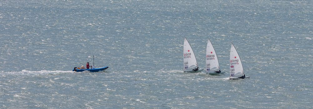 Portland harbour, United Kingdom - July 3, 2020: High Angle aerial panoramic shot of the laser class racing dinghies and a rescue boat in Portland harbour.